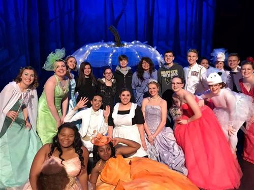 Cast and Crew of Cinderella smiling in front of pumpkin carriage